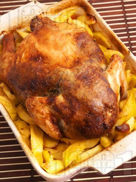 Пълнено пиле пълнено с дробчета, гъби и ориз върху с картофи на фурна - снимка на рецептата